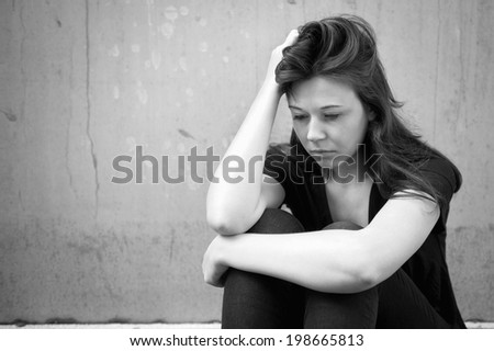Outdoor portrait of a sad young woman looking thoughtful about troubles in front of a gray wall, monochrome