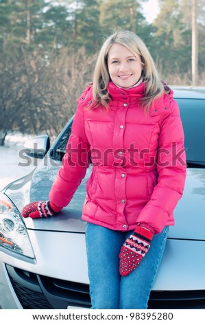 Outdoor portrait of a smiling blond woman sitting on the bonnet of the car - stock photo