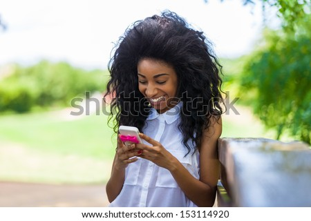 Outdoor portrait of a teenage black girl using a mobile phone - African people - stock photo