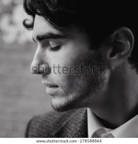 outdoor portrait of a very beautiful sexy young man, dark hair,  posing  in an old courtyard   a classic suit