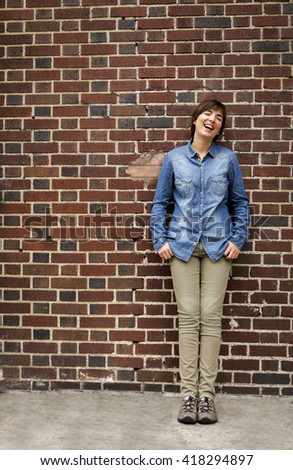 Outdoor portrait of a woman in front of a brick wall