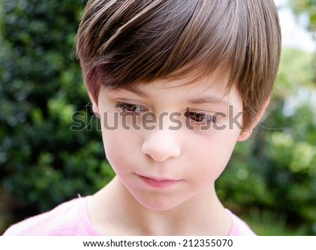 Outdoor portrait of a worried child - stock photo