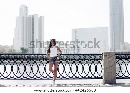 Outdoor portrait of a young beautiful fashionable happy lady posing on a street of the old city. Model wearing stylish clothes. Girl looking up. Female fashion. City lifestyle