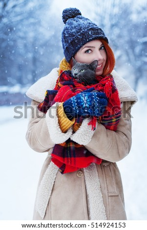 Outdoor portrait of a young beautiful happy smiling girl holding her gray cat in blanket. Model wearing stylish winter clothes. Lady looking at camera. Snowfall. Waist up