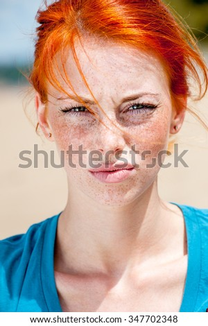 Outdoor portrait of a young beautiful redhead freckled woman looking displeased - stock photo