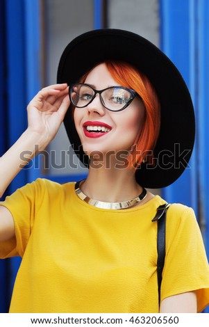 Outdoor portrait of a young beautiful smiling lady posing on the street. Model wearing stylish  accessories & clothes. Girl looking at camera. Female fashion. City lifestyle. Sunny day. Close up