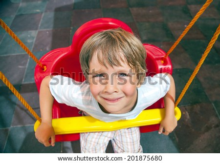 Outdoor portrait of a young boy relaxing on the swing - stock photo