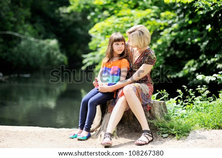 Outdoor portrait of a young mother embracing her little daughter in the park - stock photo