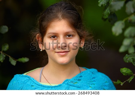 Outdoor portrait of a  young schoolgirl with dark hair and brown eyes  - stock photo