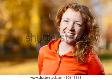 Outdoor portrait of a young smiley lady in a sports jacket - shallow DOF - stock photo