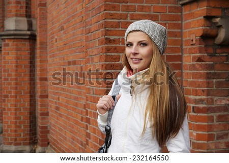 outdoor portrait of a young woman wearing woolen hat in front of red brick building - stock photo