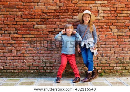 Outdoor portrait of adorable fashion kids, standing against old red brick wall - stock photo