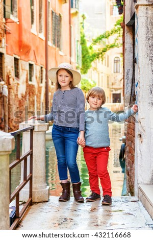 Outdoor portrait of adorable fashion kids visiting Venice, Italy. Little girl and boy walk through the old venetian streets - stock photo