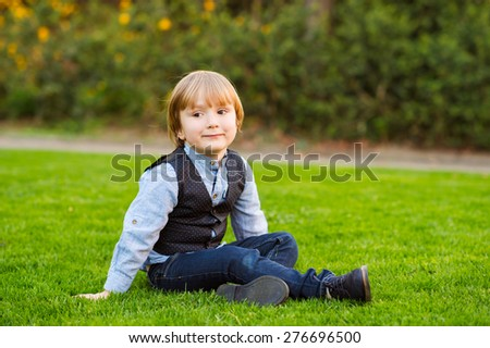 Outdoor portrait of adorable little boy of 4 years old, sitting on a lawn in the park at sunset - stock photo