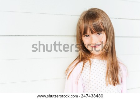 Outdoor portrait of adorable little girl against white wooden background, close up - stock photo