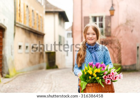 Outdoor portrait of adorable little girl of 7 years old walking in old town, holding basket full of colorful tulips, wearing warm blue pullover and scarf. - stock photo