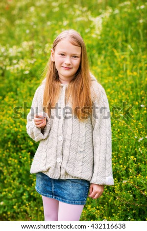 Outdoor portrait of adorable little girl of 8-9 years old, wearing beige knitted jacket, posing in green field - stock photo