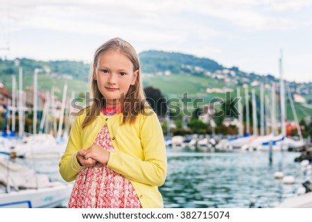 Outdoor portrait of adorable little girl of 7-8 years old, wearing party dress, resting by the lake - stock photo