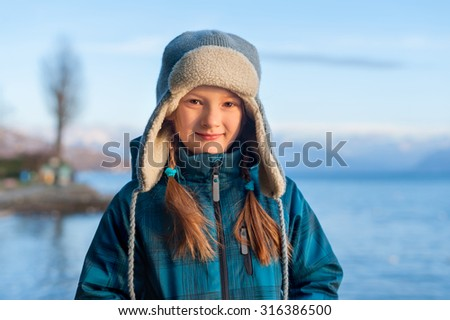 Outdoor portrait of adorable little girl on a nice winter evening, resting by the lake at sunset. - stock photo