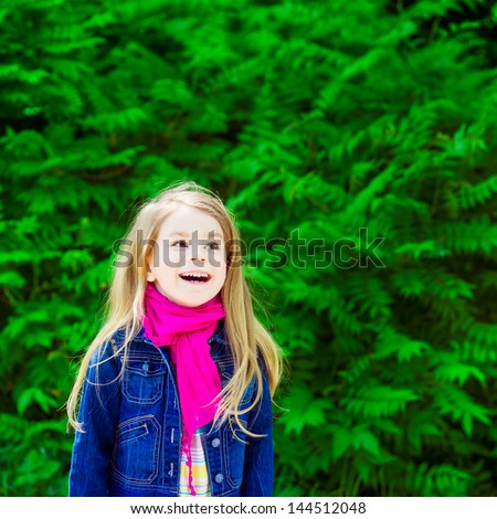 Outdoor portrait of an adorable laughing blond little girl wearing a jeans jacket and a pink scarf - stock photo