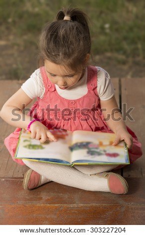 Outdoor portrait of an adorable young little girl reading a book in the garden - stock photo