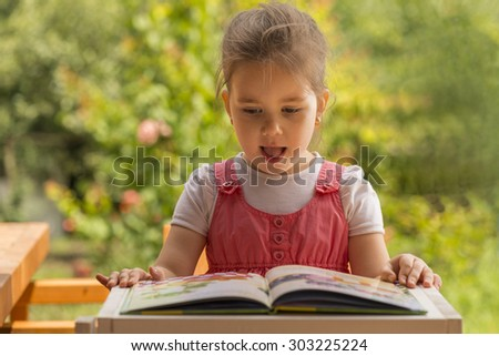 Outdoor portrait of an adorable young little girl reading a book in the garden. Expressive little girl reading loud - stock photo