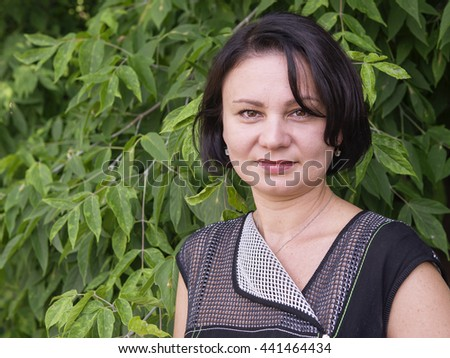 Outdoor portrait of an adult woman against a background of foliage - stock photo