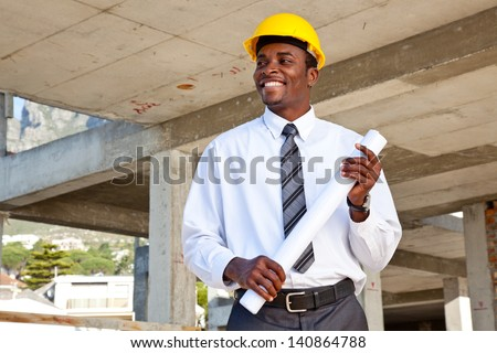Outdoor portrait of an African business man with his arms folded - stock photo