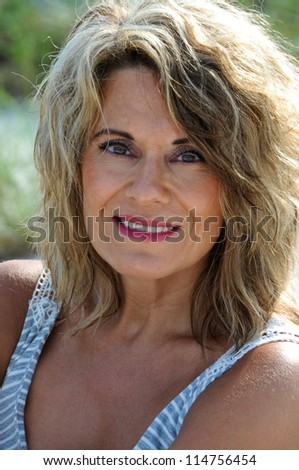 Outdoor Portrait of an Attractive Middle Aged Woman in a Sundress - stock photo
