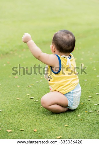 Outdoor portrait of Asian baby boy playing sitting on the green grass field in the park - stock photo