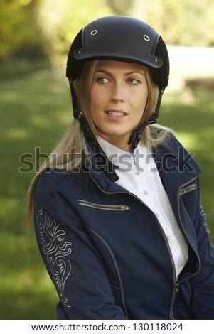 Outdoor portrait of attractive female rider in equestrian helmet, looking away. - stock photo