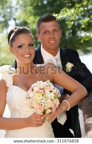 Outdoor portrait of attractive young couple on wedding-day, smiling happy.