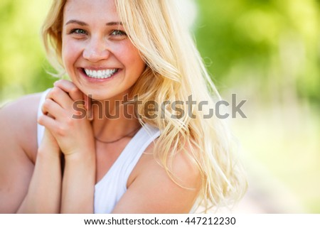 Outdoor portrait of attractive young smiling lady