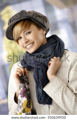 Outdoor portrait of attractive young woman wintertime, smiling.