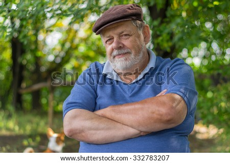 Outdoor portrait of bearded senior man resting in tree shadow