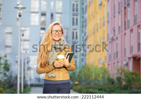 Outdoor portrait of beautiful and happy caucasian blond student girl on her way to studies smiling and looking into the camera with book in one hand and cup of coffee in the other. - stock photo
