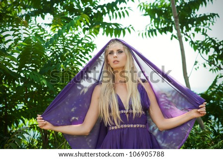 Outdoor portrait of beautiful blond woman in purple dress with veil - stock photo