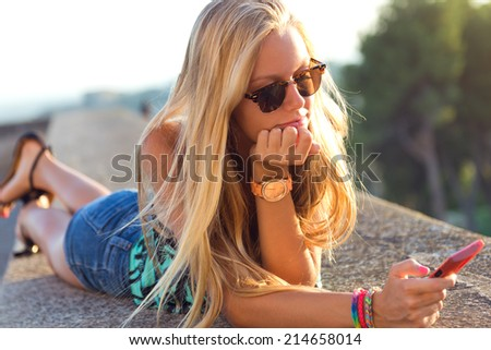 Outdoor portrait of beautiful blonde girl sitting on the roof with mobile phone.