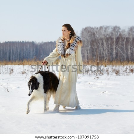 outdoor portrait of beautiful brunette woman in fur coat with wolfhound in snowy filed with winter forest on background