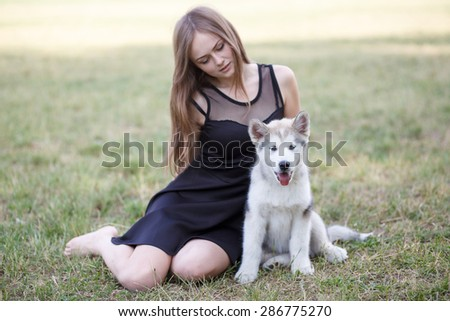 Outdoor portrait of beautiful gir and malamutes puppy