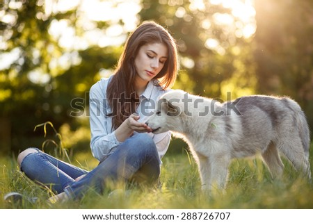 outdoor portrait of beautiful girl and malamutes puppy