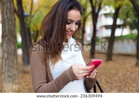 Outdoor portrait of beautiful girl chatting with mobile phone in autumn.