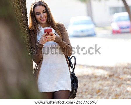 Outdoor portrait of beautiful girl chatting with mobile phone in autumn. - stock photo