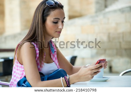 Outdoor portrait of beautiful girl drinking coffee and texting with mobile phone. - stock photo