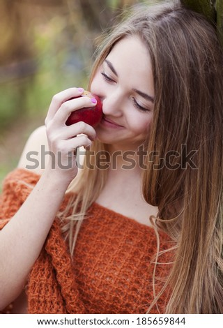 Outdoor portrait of beautiful girl holding an apple