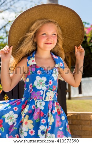 Outdoor portrait of beautiful girl in blue floral dress and beach straw hat. She holds her big hat and smile. Summer sunny day. House with wooden fence at tropical background. Mothers day. - stock photo