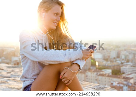 Outdoor portrait of beautiful girl sitting on the roof and listening to music. - stock photo