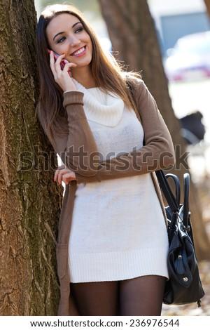 Outdoor portrait of beautiful girl talking on phone in autumn. - stock photo