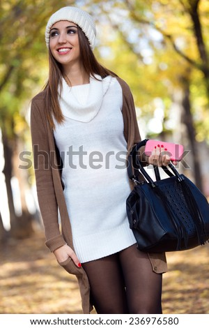 Outdoor portrait of beautiful girl walking with mobile phone in autumn. - stock photo