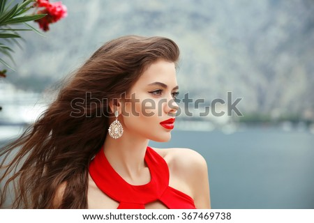 outdoor portrait of Beautiful girl with long wavy hair, red lips and fashion earrings. Brunette with curly hairstyle isolated on nature park background. - stock photo